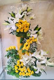2 Feet arrangement of White and Yellow Lilies Red Carnations and rajnigandha